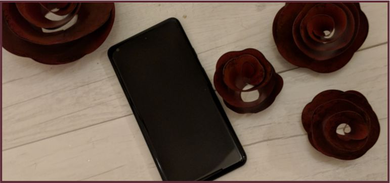 Google Pixel 2 XL laying on white wood and there are metal red roses around it.