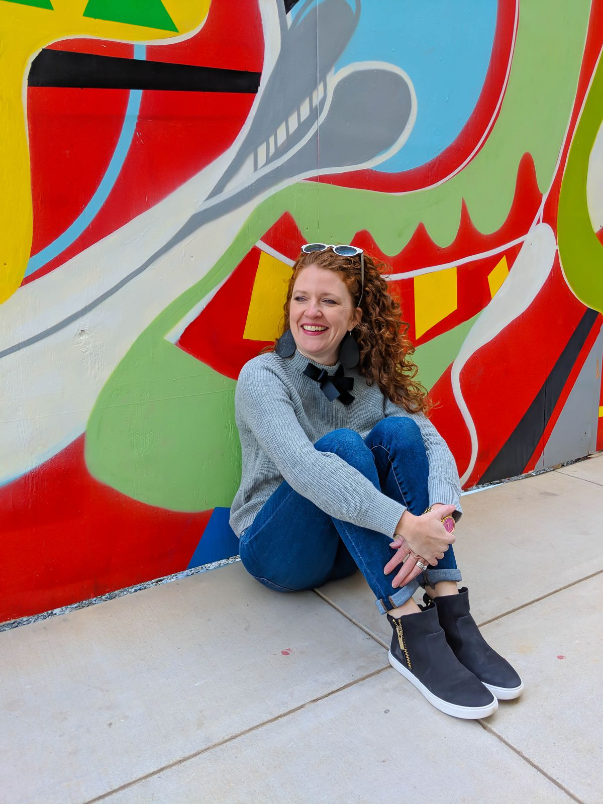 Jamie sitting with knees up and arms around legs at the mural outside of Crosstown Concourse wearing J Crew Factory bow sweater, AG jeans, Kenneth Cole black sneakers, SALT Lorna sunglasses and Nickel and Sued black cork earrings.