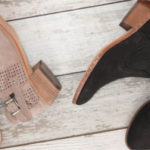 Vince Kamuto Pamma Suede Booties in Foxy and Vince Camuto Petran Bootie in Black laying on a flat lay of distressed wood.