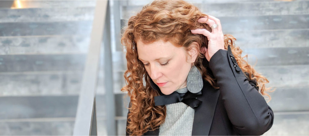 Jamie is looking down and holding hair back. She is wearing the J Crew tie neck sweater, a black tuxedo blazer and Nickel and Suede Black cork earrings.
