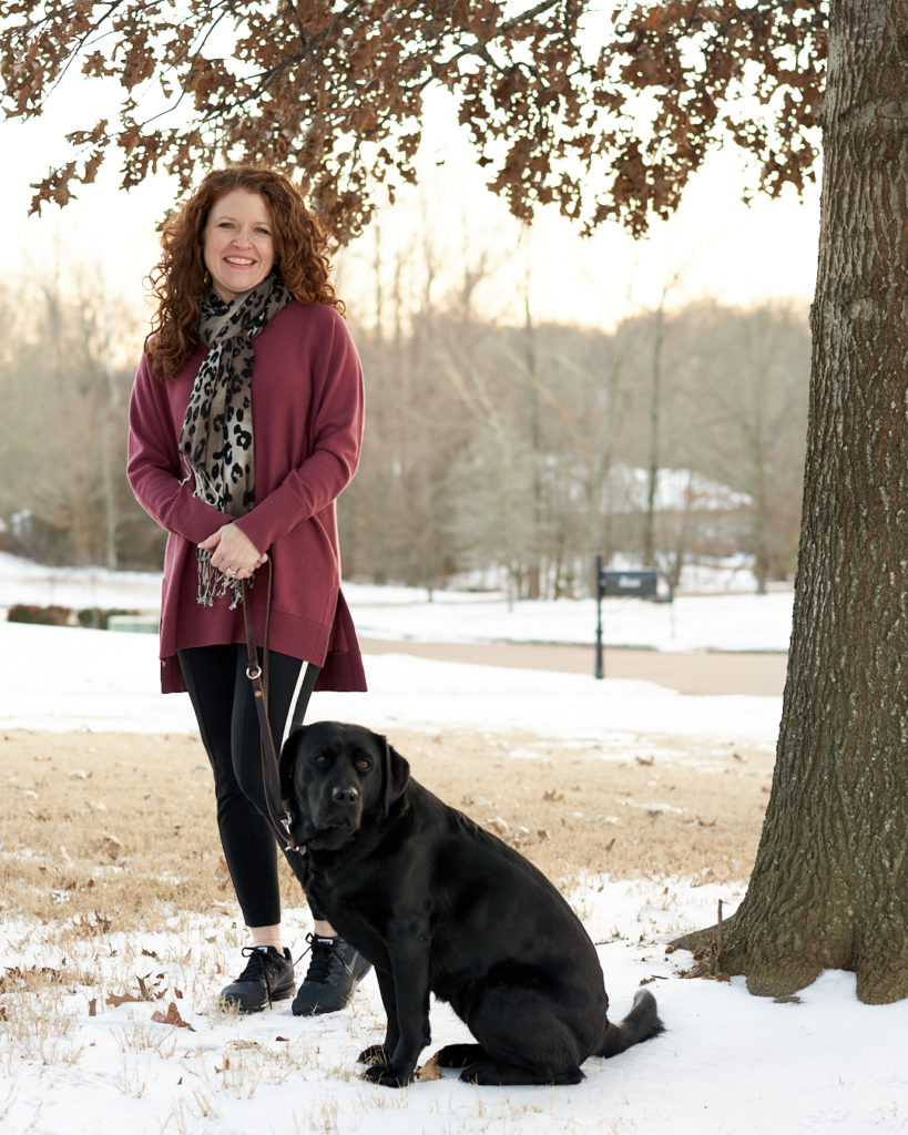 Jamie with Robin standing under a tree with Athleta wool/cashmere berry sweater and Athleta Metro 7/8 tights with white stripe down the side and Nike All Out Running shoes