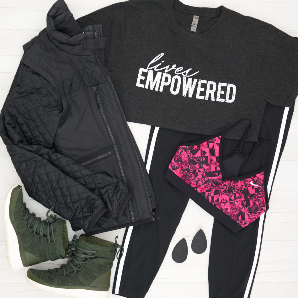 Lives Empowered GiveGood Co t-shirt with Athleta 7/8 Metro Tights and a pink and black Nike bra, Nike fleece booties and quilted jacket and Nickel and Suede black cork earrings.