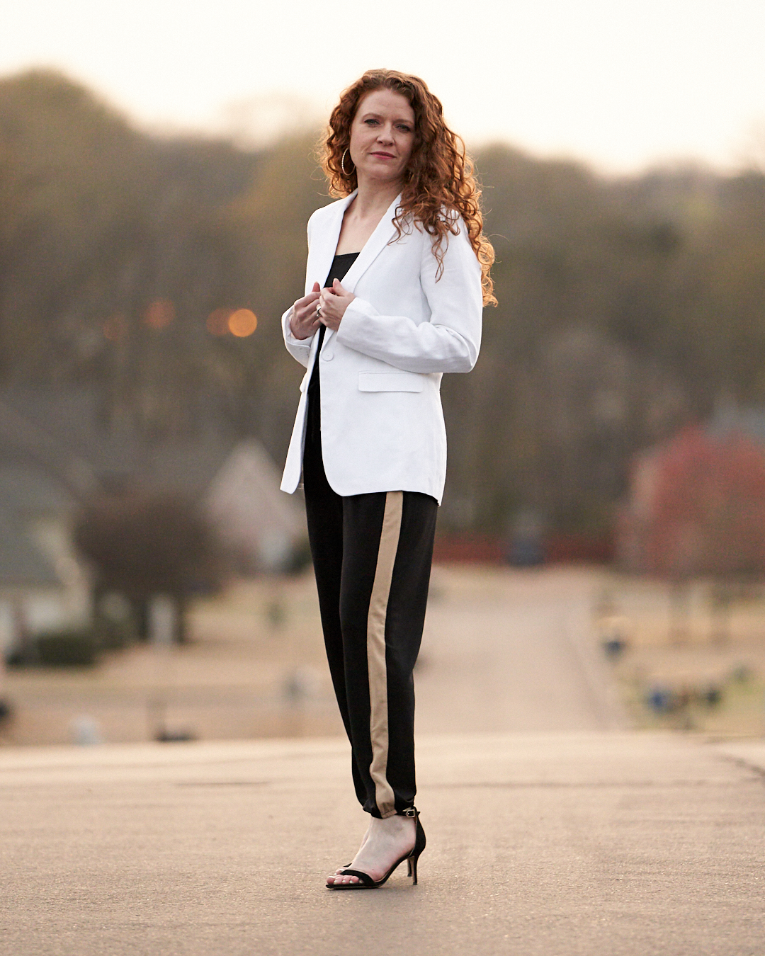 Styled jumpsuit with white blazer and black high heels and gold hoop earrings