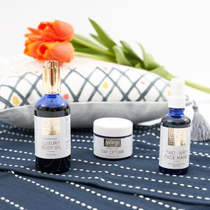 Flat Lay photo of all three products with a pillow and tulips in the background and they are on a table runner that is navy and white