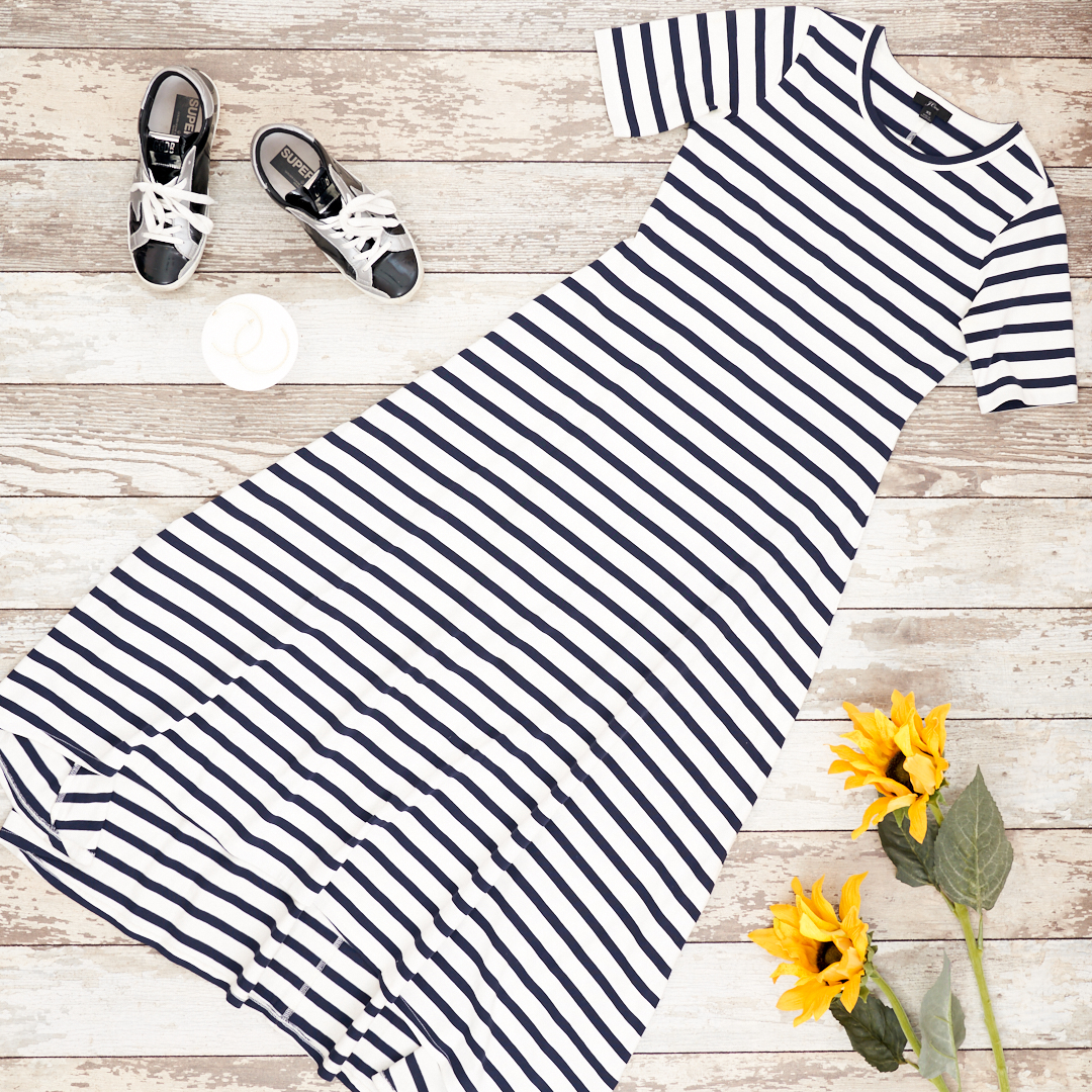 Flat lay of blue and white maxi dress from J Crew with golden goose sneakers, gold hoops and sunflowers