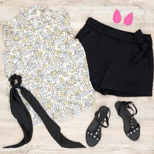Flat lay of floral sleeveless blouse and black tie waist shorts with gladiator flat sandals, black hair scarf and pink Nickel and Suede Earrings