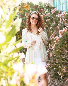 Jame is walkin by some flowers near a building wearing her striped pastel blazer , white Zara denim skirt, green headband and sunglasses