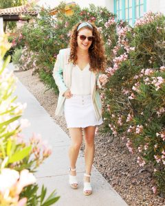 Jamie is walking along path by flowers and is wearing her stiped pastel blazer from Vici Collection, white denim skirt, cream button down camisole, headband, Kendra Scott earrings and white espadrille wedges/ Full body shot