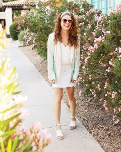 Jamie laughing while walking and wearing her spring stiped blazer , white denim skirt and cream camisole and white wedges