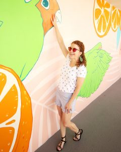 Me standing by a mural wall at the Hotel Adeline