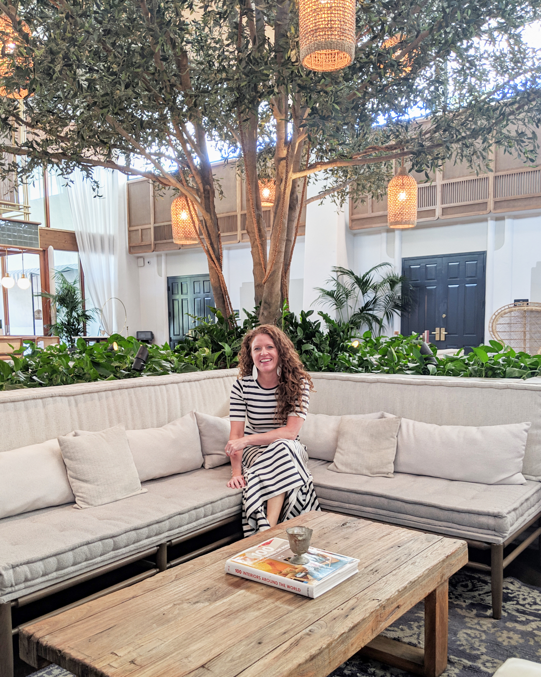 Me sitting on a couch in the lobby of The Scott Resort and Spa wearing my J Crew cottom maxi dress