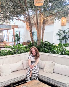 Photo of me in striped maxi dress and Golden Goose sneakers sitting on a couch in The Scott Resort in Arizona