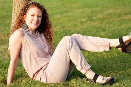 Jamie sitting in the grass with her foot kicked up showing off the shoes. Wearing a pink jumpsuit and OTBT Bushnell Sandals