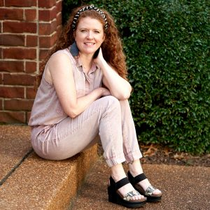 Picture of Jamie Sitting on the front porch wearing her OTBT wedges and pink jumpsuit