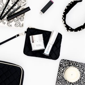 Flat lay of Alastin Skincare products in a black and white setting. They are in the middle on a black makeup bag and there are makeup brushes, a headband, lipstick and a candle around them