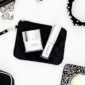 Flat lay of Alastin Products. Thye are laying on a black makeup bag and have various accessories in black and white around them