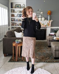 Mirror shot of me wearing the spotted slip on skirt with a plain black hi-low sweater and dressy black booties.