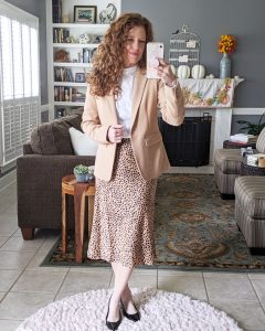 Mirrorshot of me wearing the slip-on midi skirt with a white blouse and camel blazer and pumps for a workwear outfit.