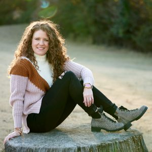 Jamie sitting on a tree stump by herself in OTBT Lakewood booties paired with jeans and a sweater