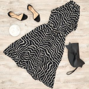 Flat lay photo of dress that is A-line and has a tie at the waist. With heels and a clutch bag